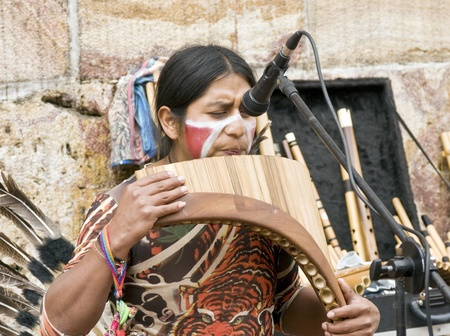 quechua indian: CUENCA, ECUADOR - MAY 27: Andean Indian plays traditional instruments on May 27, 2011 in Cuenca, Ecuador. Indigenous descendants are found in the towns of the Andes mountain range in South America.