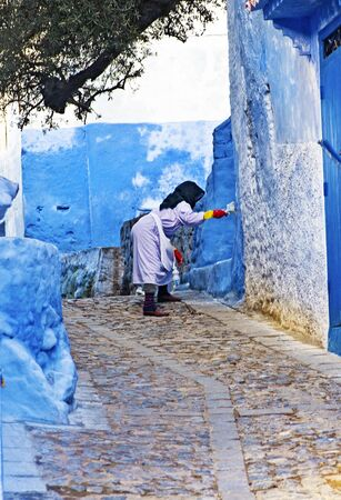 asbestos: CHEFCHAOUEN, MOROCCO- JANUARY 17: Local Moroccan woman painting her home facade on January 17, 2010 in Chefchaouen, Morocco. This is a unique medieval blue medina by the RIF Mountains.