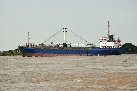 Cargo Ship Navigating Across River photo