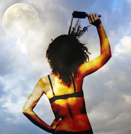 Woman brushing curly hair in front of a full moon