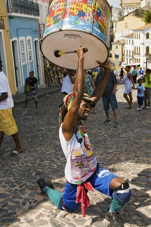 SALVADOR, BRAZIL - DECEMBER 8: Samba street performer holding drum while playing in Pelourinho historic center in Salvador, Brazil on December 8, 2012.   Editorial