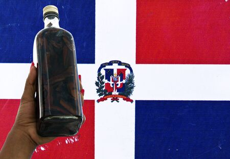 Mamajuana, the Dominican Republic Typical Beverage on a Rustic Dominican Flag photo