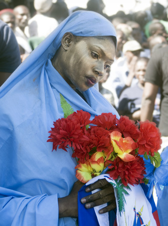 CAP-HAITIEN, HAITI - NOV 18,  Unidentified Haitian woman holding flowers and a flag while waiting for the president visit, during the political manifestation on November 18, 2013 in Cap-Haitien, Haiti Stock Photo - 23889323