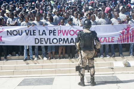CAP-HAITIEN, HAITI - NOV 18,  Anti-Riot Soldier stands in front of crowd asking for peace and development while waiting for the president Martelli visit on November 18, 2013 in Cap-Haitien, Haiti Stock Photo - 23919150