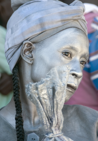CAP-HAITIEN, HAITI - NOV 18,  Unidentified Haitian woman painted in silver waiting for the president visit with life improvement expectations on November 18, 2013 in Cap-Haitien, Haiti Stock Photo - 23918918