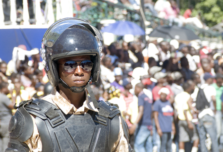 CAP-HAITIEN, HAITI - NOV 18,  Anti-Riot Soldier stands in front of crowd while waiting for the president Martelli visit on November 18, 2013 in Cap-Haitien, Haiti Stock Photo - 23969805