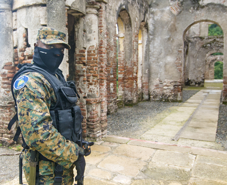MILOT, HAITI - NOV 17, Masked soldier guarding the ruins of Palace Sans-Soici on November 17, 2013 in Milot, Haiti  Stock Photo - 24101285