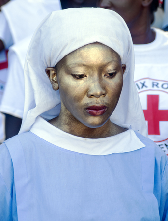 CAP-HAITIEN, HAITI - NOV 18,  Unidentified Haitian painted nurse waiting for the president visit and expecting health system improvement on November 18, 2013 in Cap-Haitien, Haiti Stock Photo - 24270259