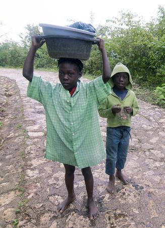 MILOT, HAITI - NOV 17, Unidentified Haitian kids carrying their goods on a steep mountain road on November 17, 2013 in Milot, Haiti
