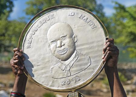 port au prince: Cap-Haitien, Hait� - 18-NOV-partidario presidente Michel Martelly muestra una pancarte con su imagen durante su visita a Nazareth Plaza p�blica el 18 de noviembre de 2013, de Cap-Haitien, Hait�