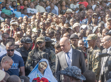 acknowledge: CAP-HAITIEN, HAITI -NOV 18, President of Haiti Michel Martelly acknowledge protester woman on Nazareth Street on a visit to Cap-Haitien on November 18, 2013 in Cap-Haitien, Haiti Editorial