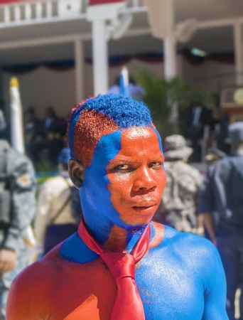 CAP-HAITIEN, HAITI - NOV 18, Supporter of president Martelly in full painted body with Haitian flag colors expecting reforms on the president visit on November 18, 2013 in Cap-Haitien, Haiti Stock Photo - 24618677