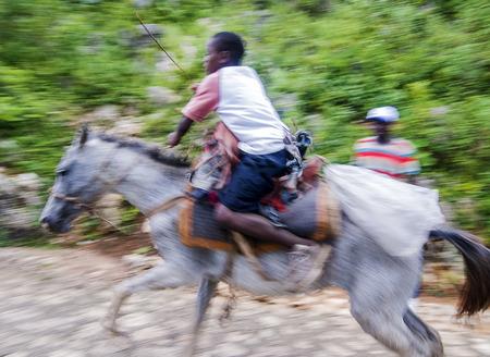 MILOT, HAITI - NOV 17, Unidentified Haitian boy riding his fast horse on a steep mountain road on November 17, 2013 in Milot, Haiti