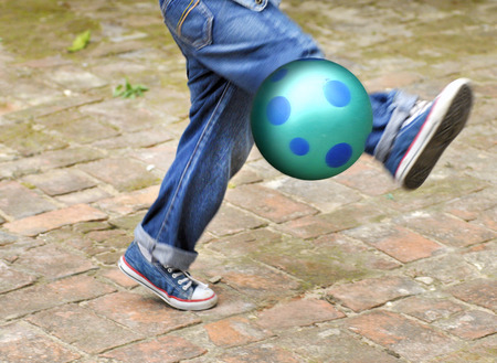Boy in Motion Kicking a Ball