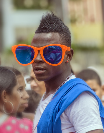 SANTO DOMINGO, DOMINICAN REPUBLIC - MARCH 2  Unidentified man wearing huge party glasses at the public annual  Carnival in the Malecon streets on March 2, 2014 in Santo Domingo, Dominican Republic