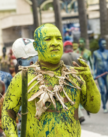 SANTO DOMINGO, DOMINICAN REPUBLIC - MARCH 2 Unidentified man painted in green and smoking at the public annual Carnival in the Malecon streets on March 2, 2014 in Santo Domingo, Dominican Republic