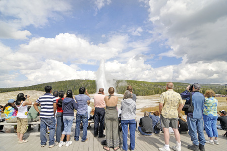 YELLOWSTONE NATIONAL PARK, WYOMING - SEPTEMBER 6: Tourists photographing Old Faithful Geyser in Yellowstone National Park on September 6, 2009. Banco de Imagens - 57457112