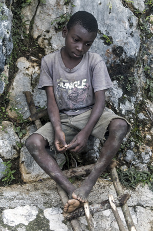 MILOT, HAITI - NOVEMBER 17, 2013: Unidentified boy portraits the sad reality of the extremely poor living conditions in the poorest country on the American continent. Banco de Imagens - 87318313