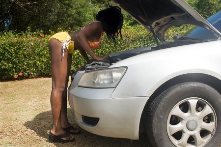 Woman checking broken car engine on a very sunny summer day Banco de Imagens