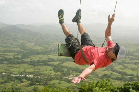 Scared man swinging over the mountains Banco de Imagens - 146003777