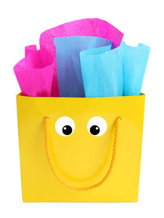tissue paper: Yellow gift bag stuffed with pink and turquoise tissue paper with a smiley face on it, isolated on white Stock Photo