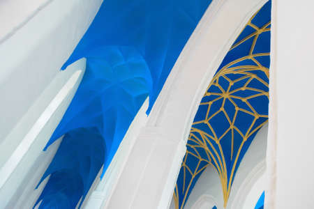 nave: Blue and yellow ornamental church ceiling nave and white arches, fragment Stock Photo