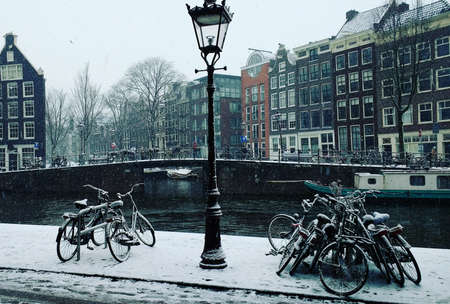 Snow-covered bikes and a lampost stand against a the background of classic Amsterdam canal houses overlooking the canal Editorial