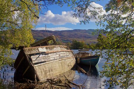 Two Decaying Derelict Wooden Boats Washed Up on Shoreline