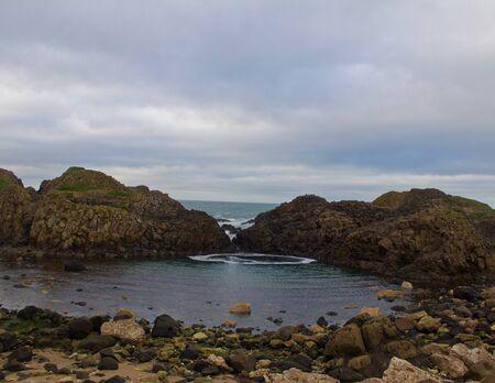 Blue Tidal Pool Surronded by Rocks on Irish Beach Stock Photo