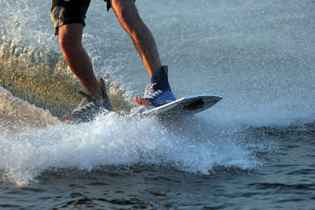 boarders: close up of a water ski boarders boots with open toes. Board is creating a wave  splash. Stock Photo