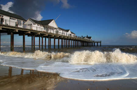 southwold: Southwold Pier in Suffolk, UK. White pier buildings against a blue sky with waves breaking on a sandy beach in the forground. Stock Photo