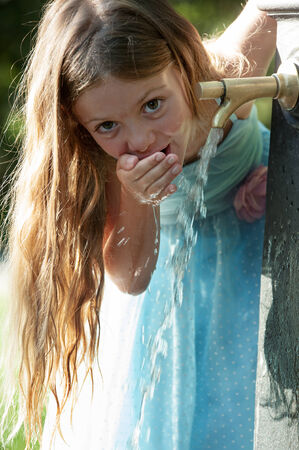 Little quenches thirst at the fountain photo