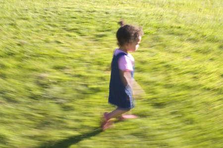 A young mixed race girl runs through a grassy field Stock Photo - 268158