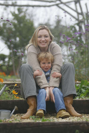 A young mother and her son in a flower filled garden photo