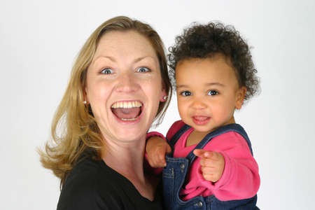 A young mother with a mixed race child laughing and pointing at the camera Stock Photo - 275882