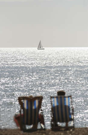 A couple on an English beach seated in deck chairs look towards a boat on the horizon photo