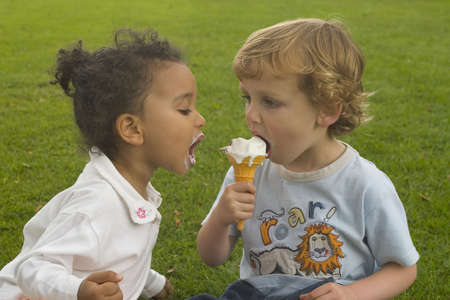 Two young children sharing an ice cream cone.
