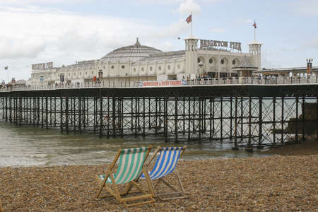 Brighton Pier with 2 empty deck chairs in the foreground