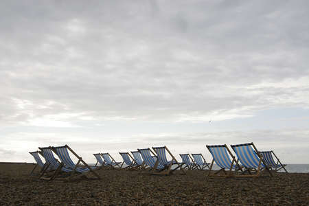A group of empty deckchairs on a cloud covered beach in the early morning photo
