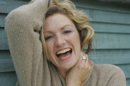 Une femme de blonde dans ses années '30 supportant ses cheveux et riant de l'appareil-photo