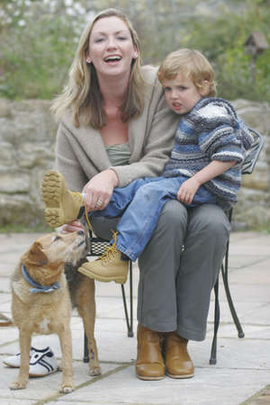 A young mother does up the boot laces of her son while the family dog looks on photo