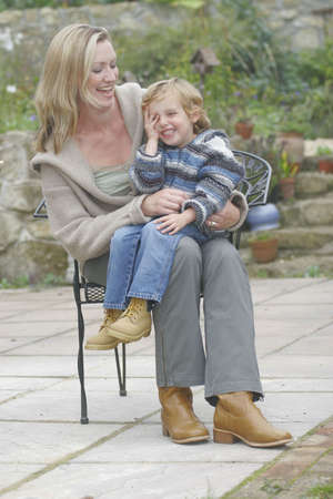 A young mother and her son together on a chair in the garden photo