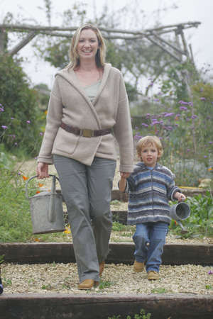 A young mother walking with her son through a flower filled garden carrying watering cans photo