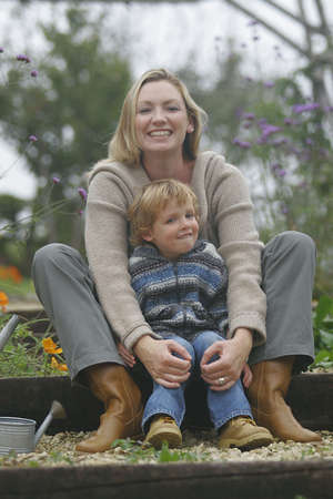 A young mother and her son together in a flower filled garden photo