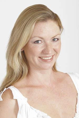 unmarried: Una mujer joven del blonde en una tapa baja blanca del cuello tirada en un fondo blanco del estudio