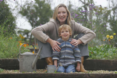 A young mother and her son in a flower filled garden with watering cans. photo