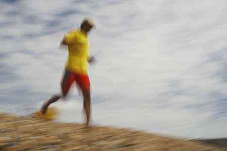 rescuing: A motion blurred shot of a lifeguard running down the beach