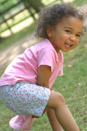 vaderlijk: Een jong meisje gemengd ras met plezier en lachen naar de camera