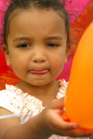 A young mixed race child holding balloons at a party Stock Photo - 275929