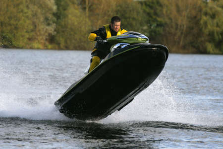 dry suit: A jet ski and its rider jumping clear of the watr